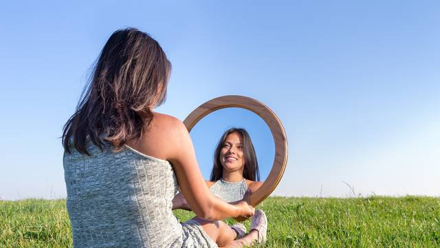 Woman in nature viewing her mirror image