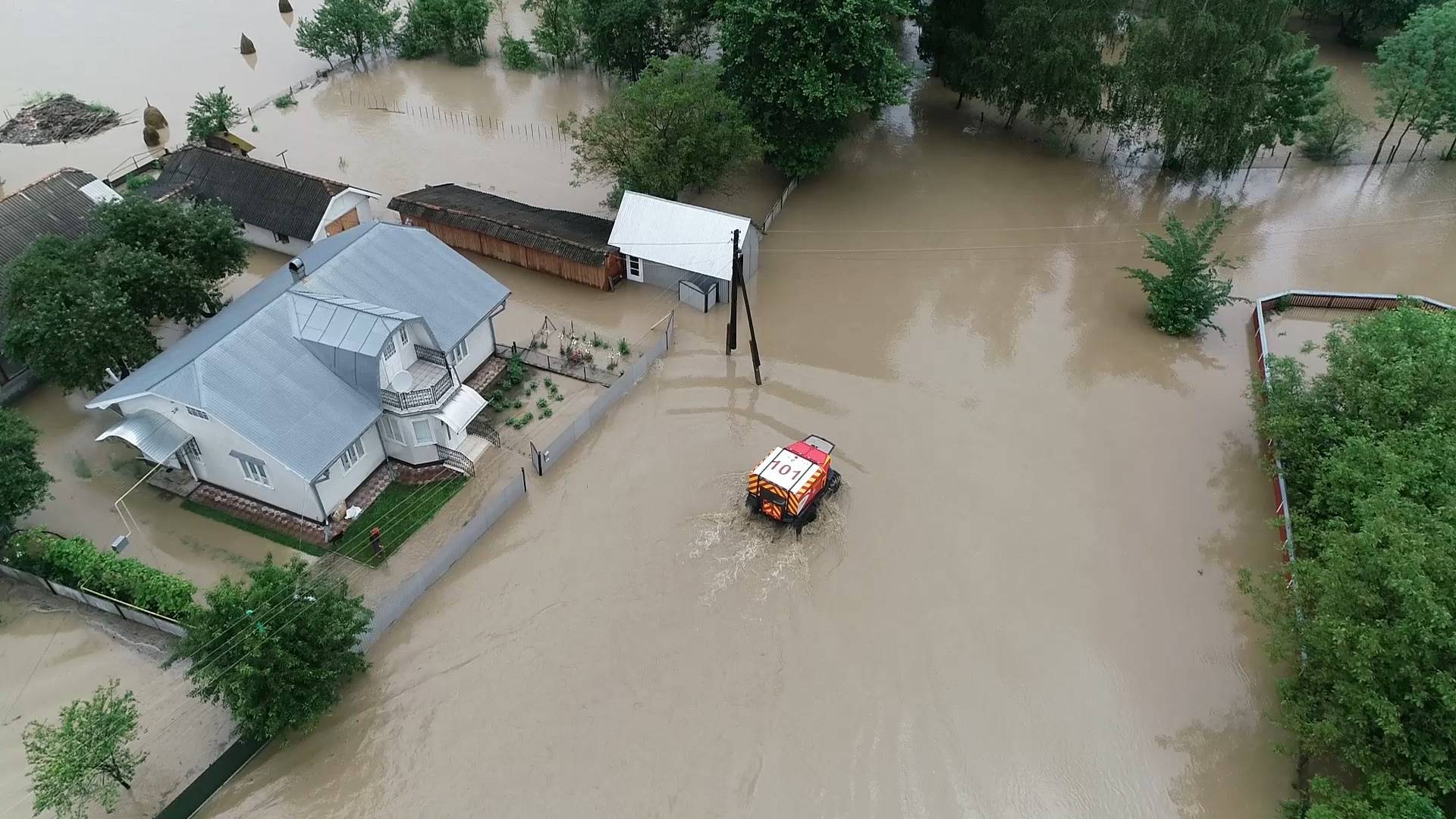 Rescuers ride inside amphibious vehicle through flooded residential area in Chernivtsi region