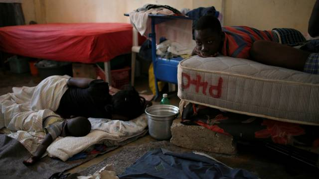 People wake up in the morning after sleeping at a partially destroyed church used as a shelter after Hurricane Matthew hit Jeremie