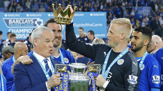 Leicester City manager Claudio Ranieri holds the trophy as he celebrates winning the Barclays Premier League with Kasper Schmeichel and teammates