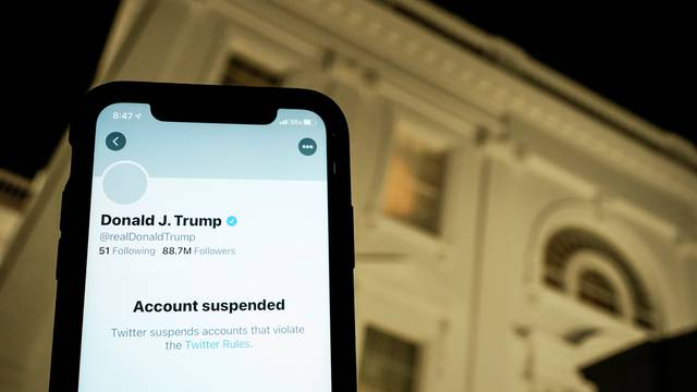 A photo illustration shows the suspended Twitter account of U.S. President Donald Trump on a smartphone and a lit window in the White House residence in Washington