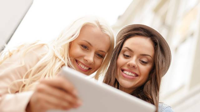 two beautiful girls looking into tablet pc