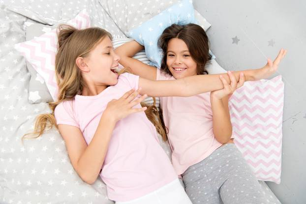 Slumber party concept. Girls just want to have fun. Invite friend for sleepover. Best friends forever. Consider theme slumber party. Slumber party timeless childhood tradition. Girls relaxing on bed