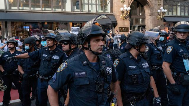 New York Police Department (NYPD) officers stand guard during a march demanding Donald Trump and Mike Pence leave office near Herald Square in the Manhattan borough of New York City