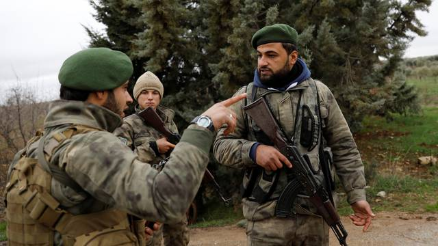 Members of Turkey-backed Free Syrian Army police forces secure the road as they escort a convoy near Azaz