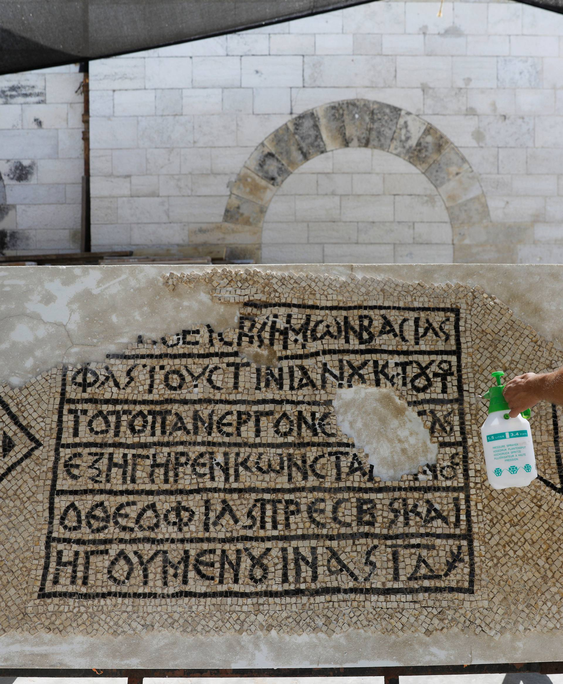 A conservationist works on a 1500-year-old mosaic floor bearing a Greek writing, discovered near Damascus Gate in Jerusalem's Old City, as it is displayed at the Rockefeller Museum in Jerusalem