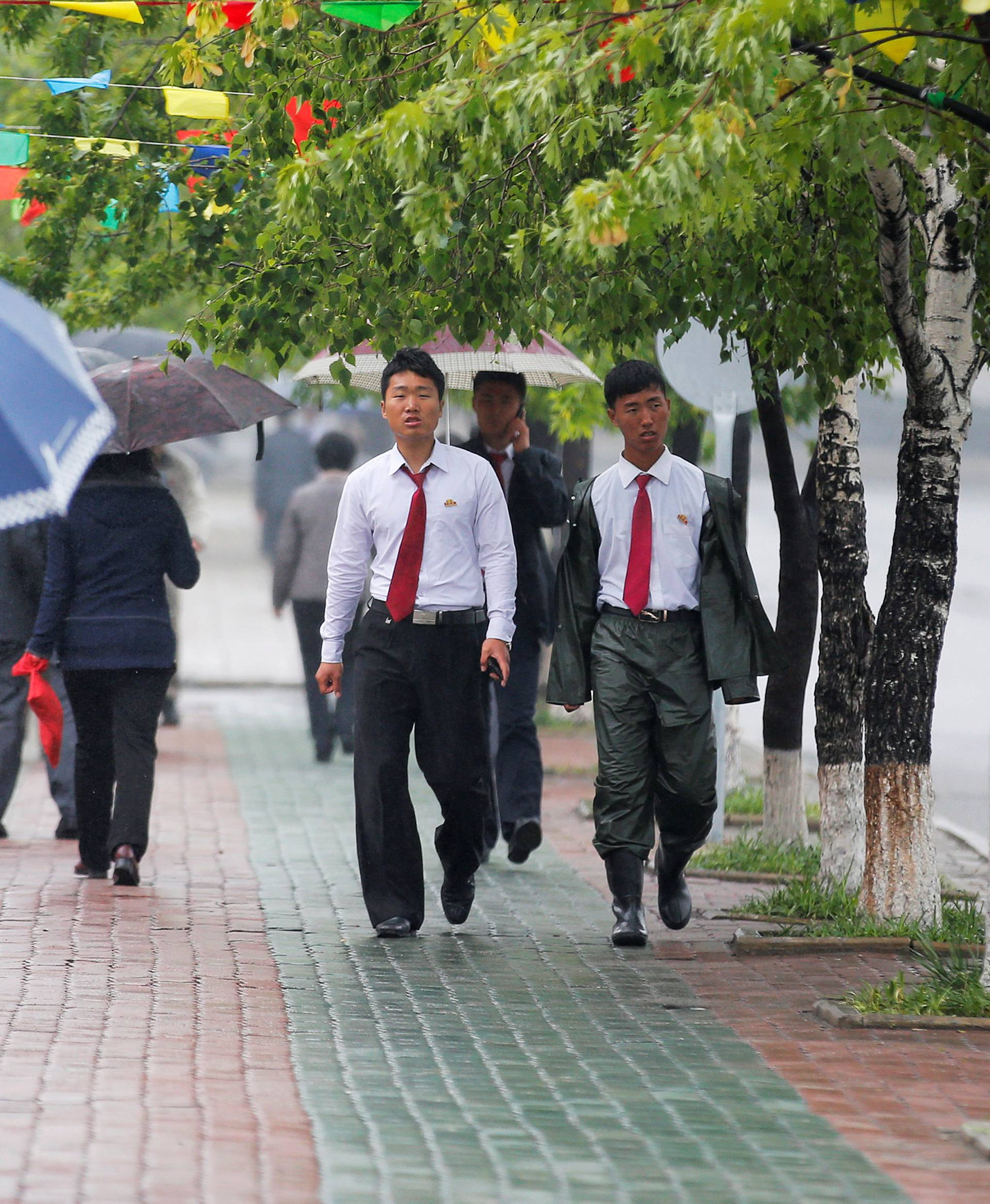 People walk in the rain near April 25 House of Culture, the venue of Workers' Party of Korea (WPK) congress in Pyongyang