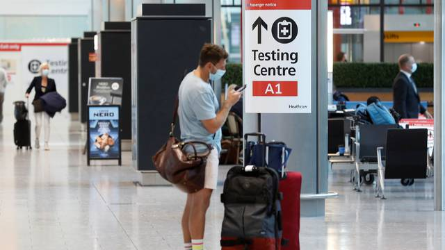 A passenger stands next to a COVID-19 testing centre sign in the International arrivals area of Terminal 5 in London's Heathrow Airport