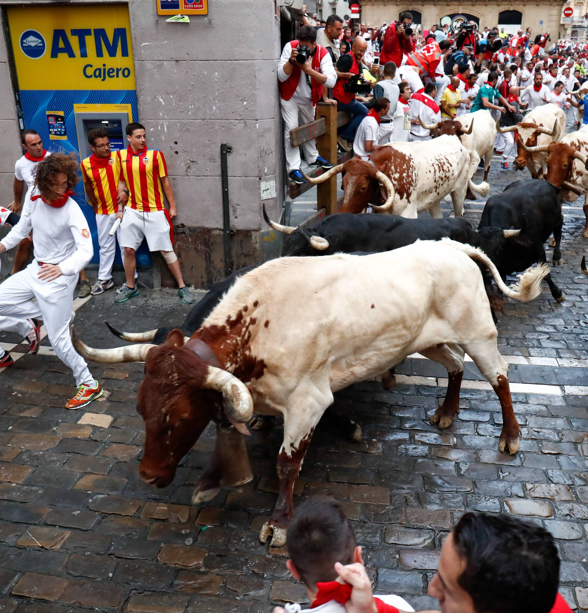 Participants run next to Vitoriano del Rio fighting bulls on Estafeta street on the fourth bullrun of the San Fermin festival in Pamplona, northern Spain on July 12, 2018
