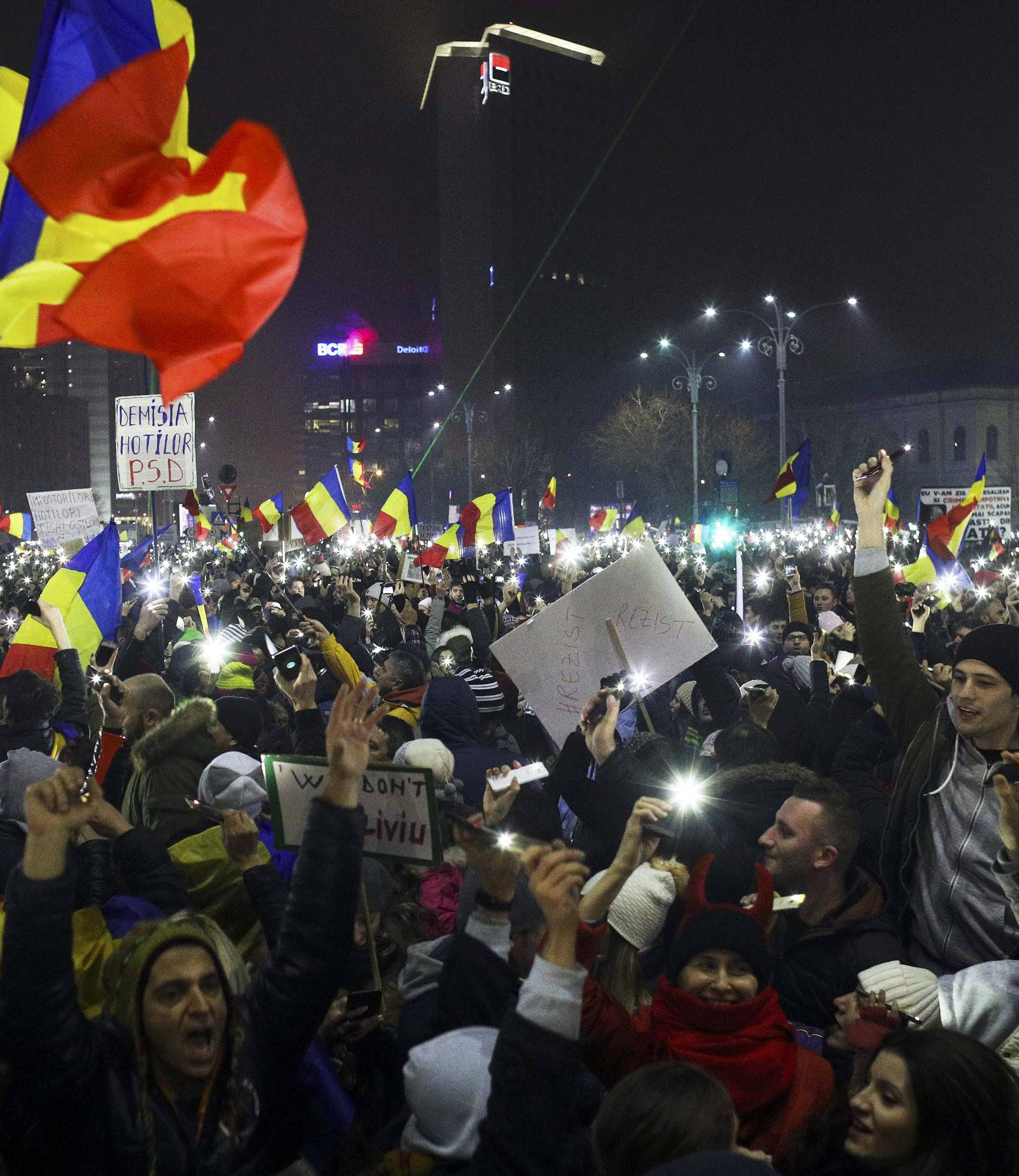 Protesters light their mobiles as they take part in a demonstration in Bucharest