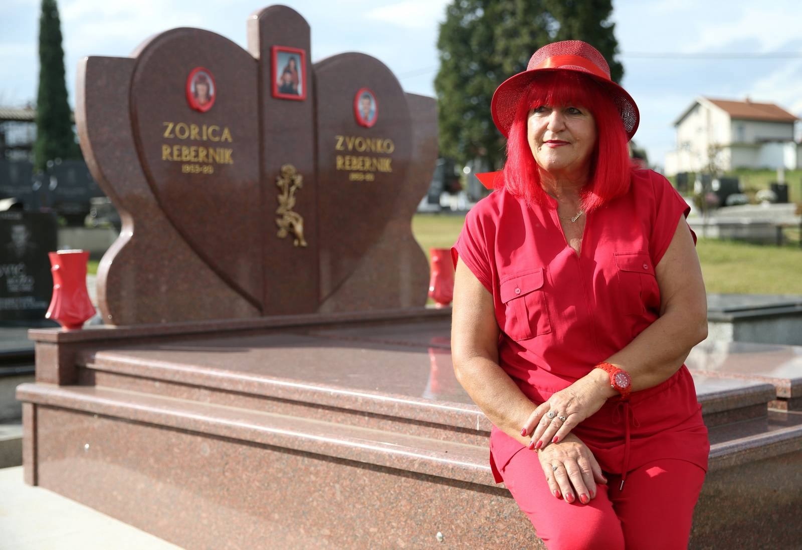 Zorica Rebernik, obsessed with the red color, sits on her grave in the village of Breze near Tuzla