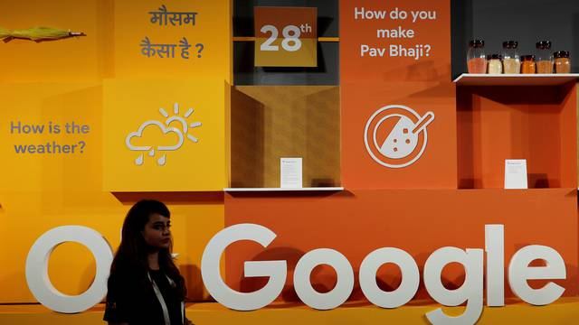 FILE PHOTO: A woman walks past the logo of Google during an event in New Delhi
