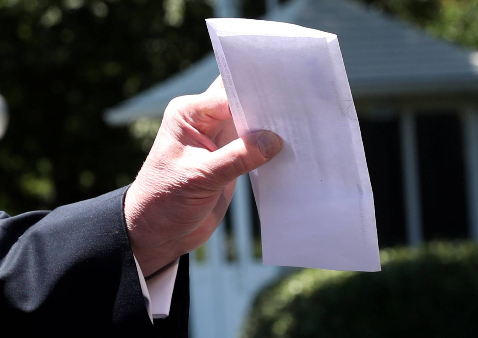 U.S. President Trump holds copy of regional asylum plan as he departs for travel to Iowa from the White House in Washington