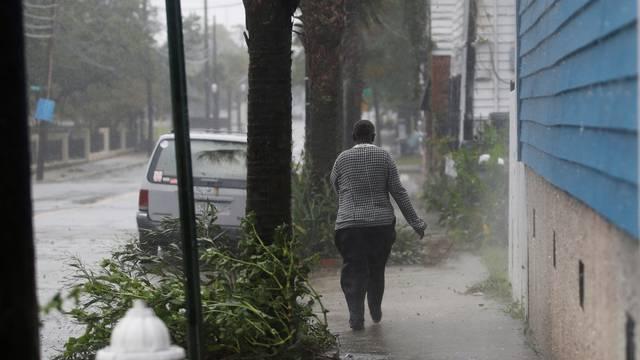 A woman walks down a street during Hurricane Dorian in Charleston