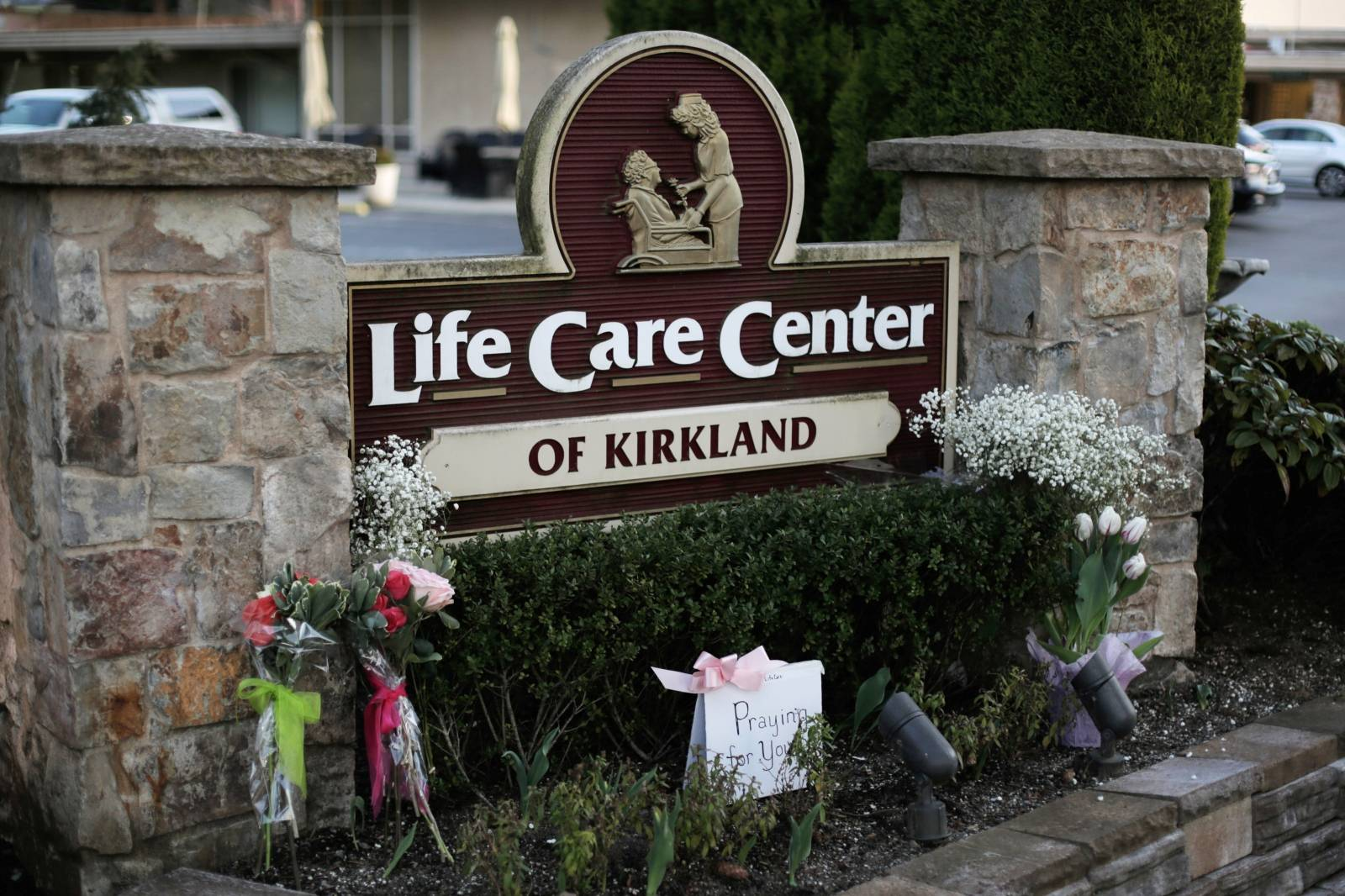 A homemade sign and flowers from community members are seen near the entrance to the Life Care Center of Kirkland