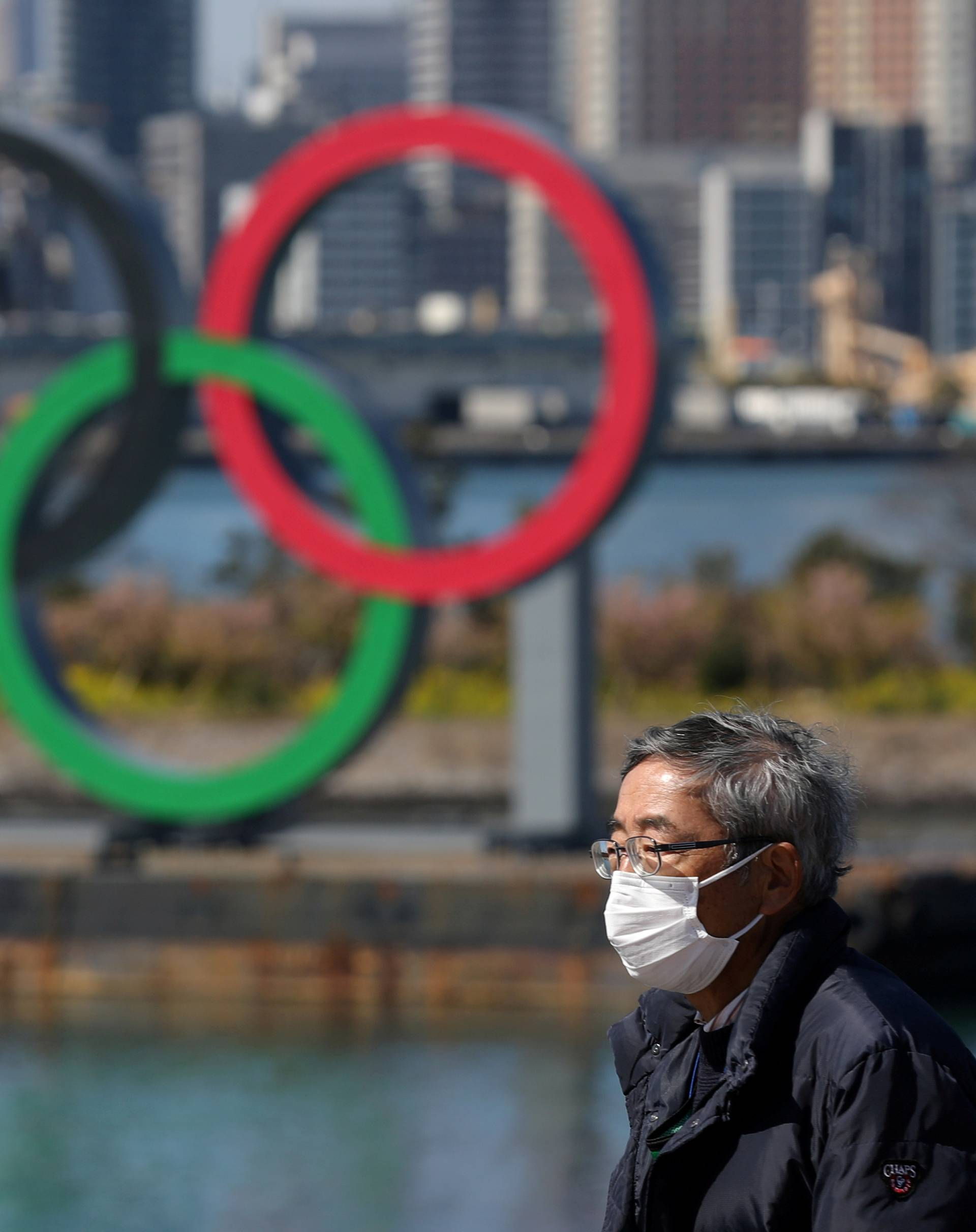 FILE PHOTO: A man walks in front of the Olympicringsat the waterfront area at Odaiba Marine Park in Tokyo