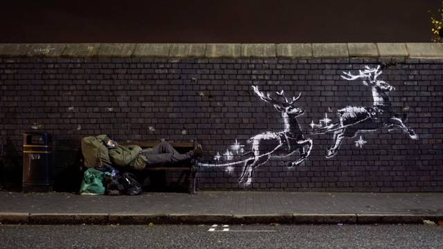 A man lays on a bench next to a new mural by Banksy in Birmingham