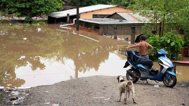 Man looks at houses at an area flooded by the Chamelecon river after the passing of Storm Iota, in La Lima