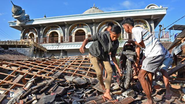 People recover a motorcycle from a damaged home near a mosque after a strong earthquake in  Gunungsari, West Lombok