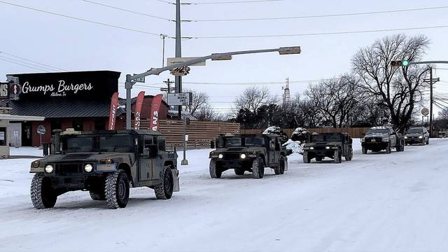 Military vehicles transport residents to designated warming centers in Abilene