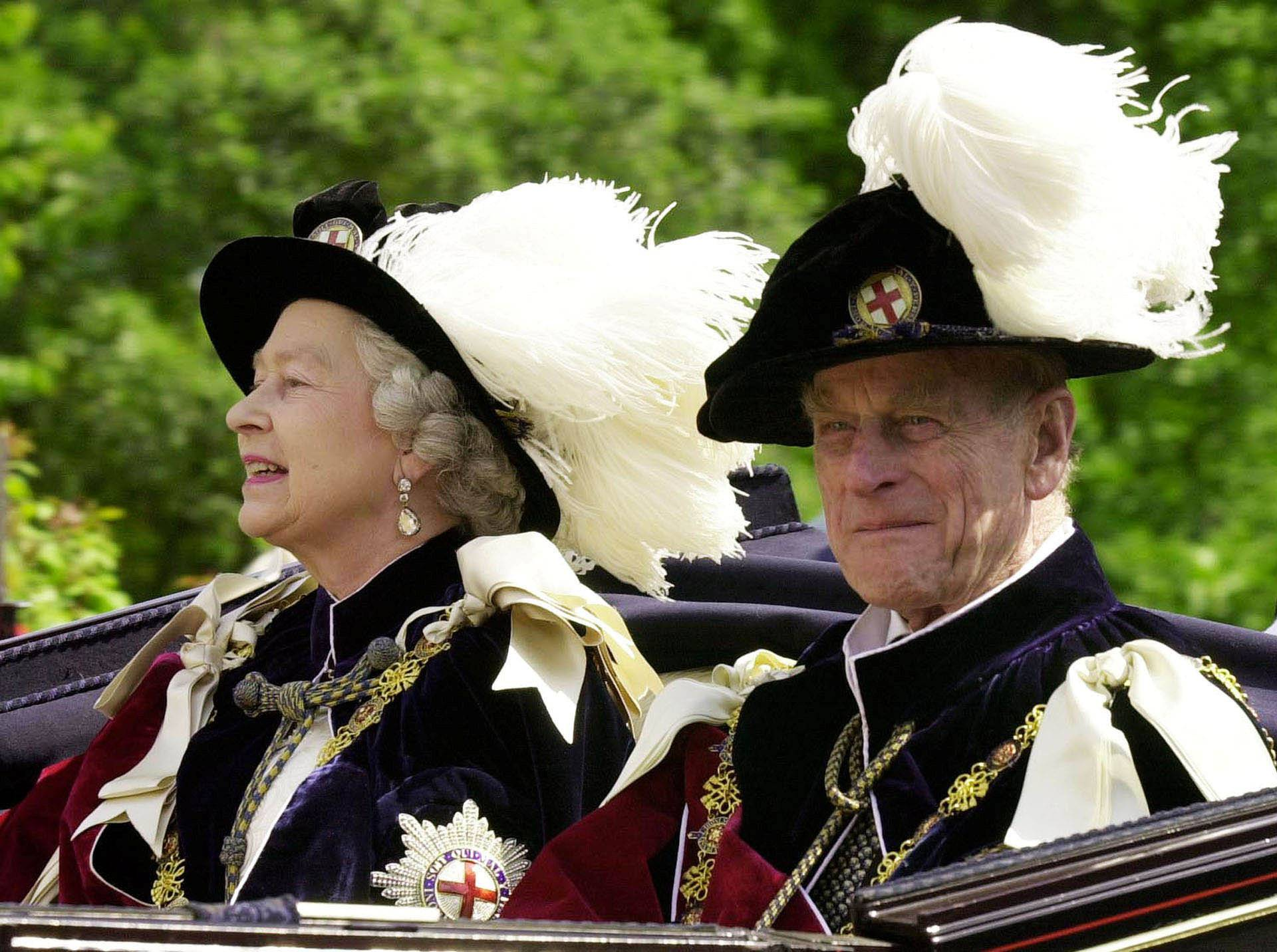 FILE PHOTO -  File photo of Britain's Queen Elizabeth II and Prince Phillip, the Duke of Edinburgh, riding in an open-topped carriage to Windsor Castle