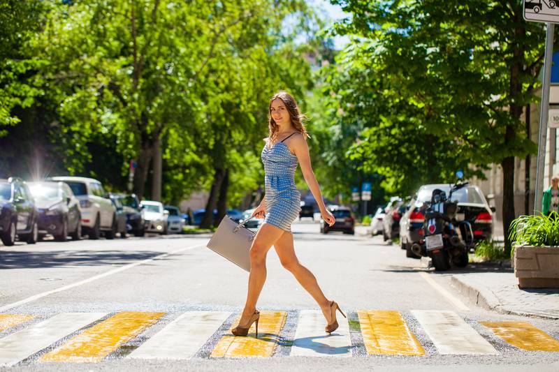 Young beautiful woman in a blue short dress walking on the road