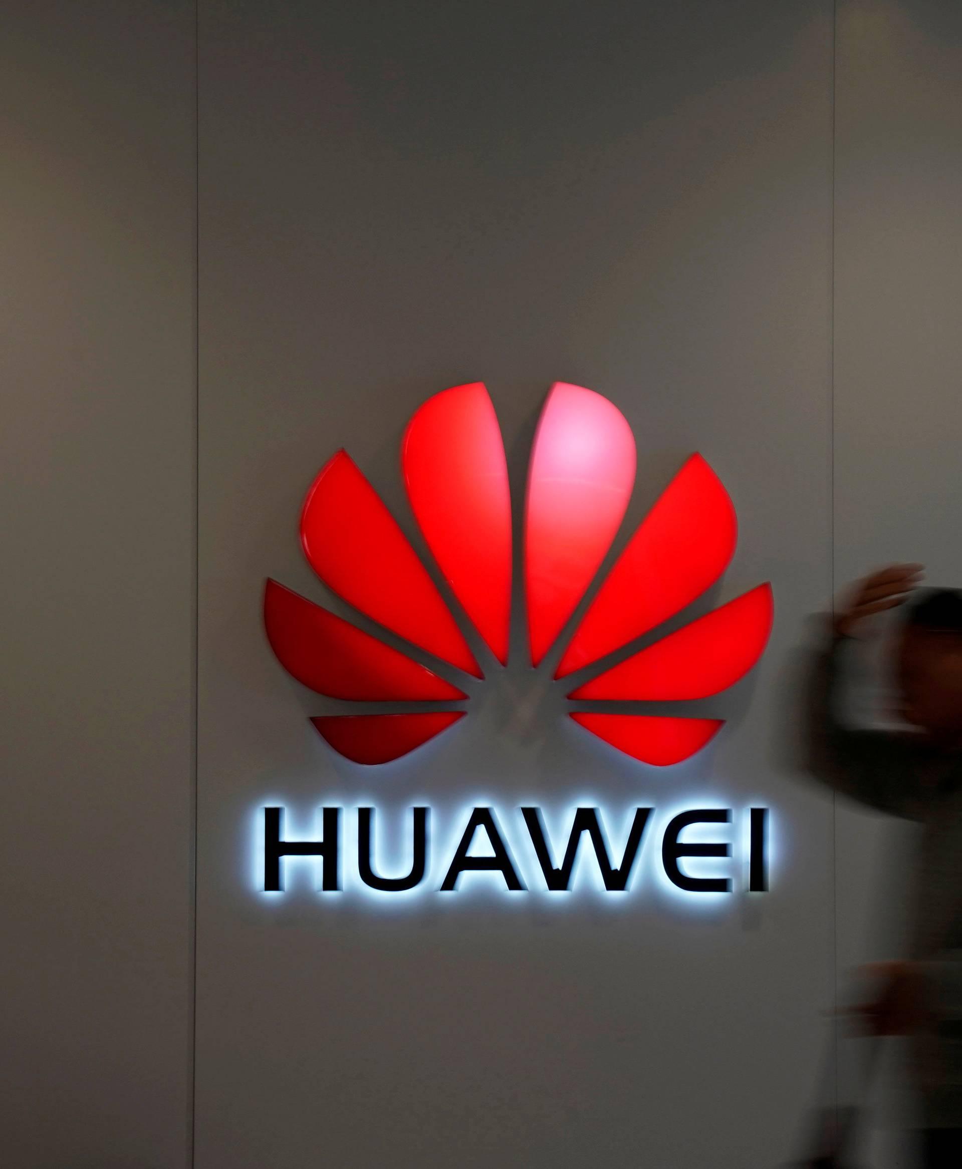 FILE PHOTO: Man walks by a Huawei logo at a shopping mall in Shanghai