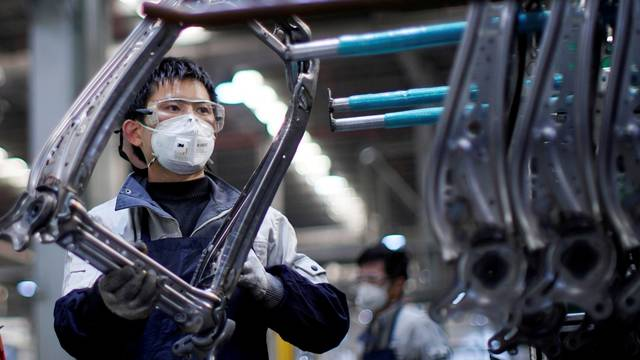 FILE PHOTO: Employee wearing a face mask works on a car seat assembly line at Yanfeng Adient factory in Shanghai