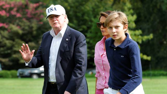 President Donald Trump waves as he with First Lady Melania Trump and their son Barron walk on South Lawn of the White House