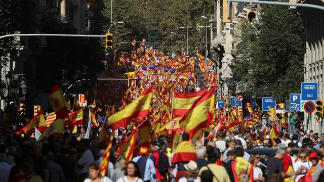 People wave Spanish and Catalan flags as they attend a pro-union demonstration organised by the Catalan Civil Society organisation in Barcelona