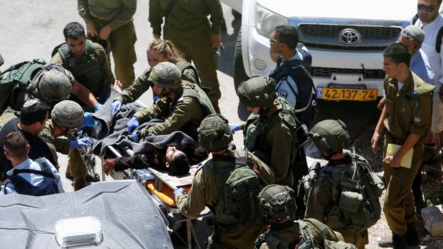 Israeli forces carry on a stretcher a Palestinian assailant after he was shot by Israeli troops at the scene of a stabbing attack in the West Bank city of Hebron