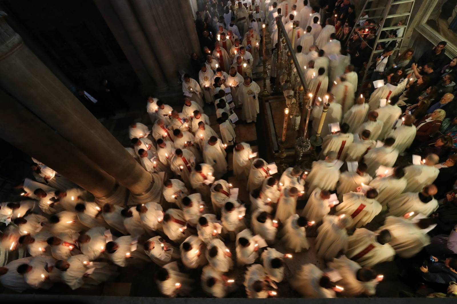 Worshippers take part in a procession during the Catholic Washing of the Feet ceremony on Easter Holy Week in the Church of the Holy Sepulchre in Jerusalem's Old City