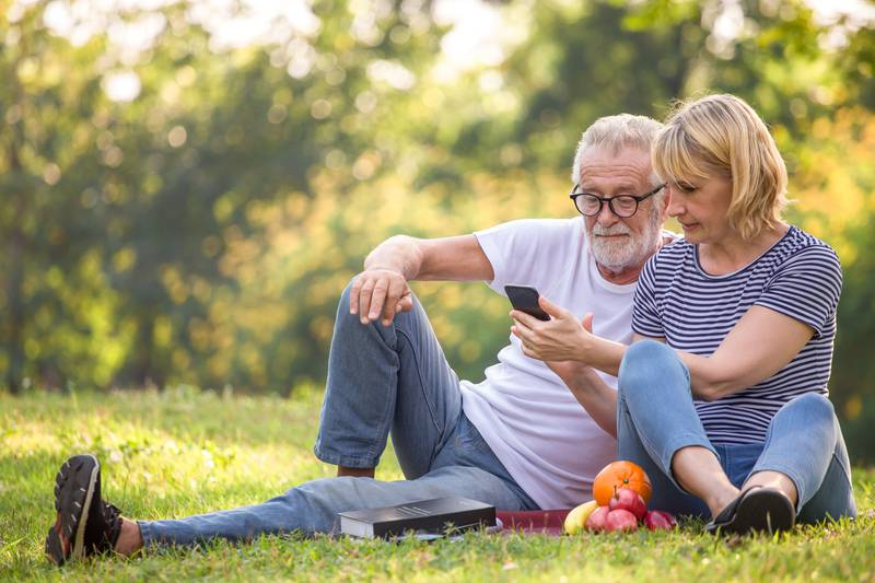 Happy senior couple relaxing in park using smartphone together .