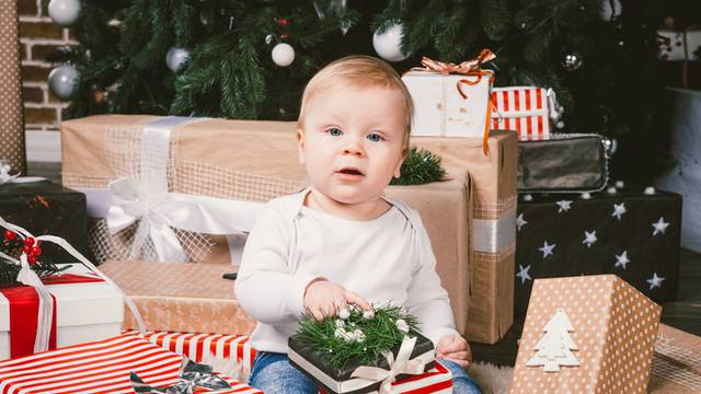 theme winter and Christmas holidays. Child boy Caucasian blond 1 year old sitting home floor near Christmas tree with New Year decor on shaggy carpet skin receives gifts, opens gift boxes in evening