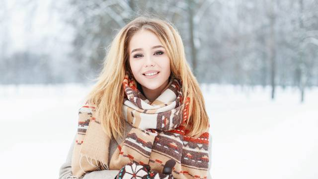 Young beautiful girl with a cute smile in vintage scarf and mitt