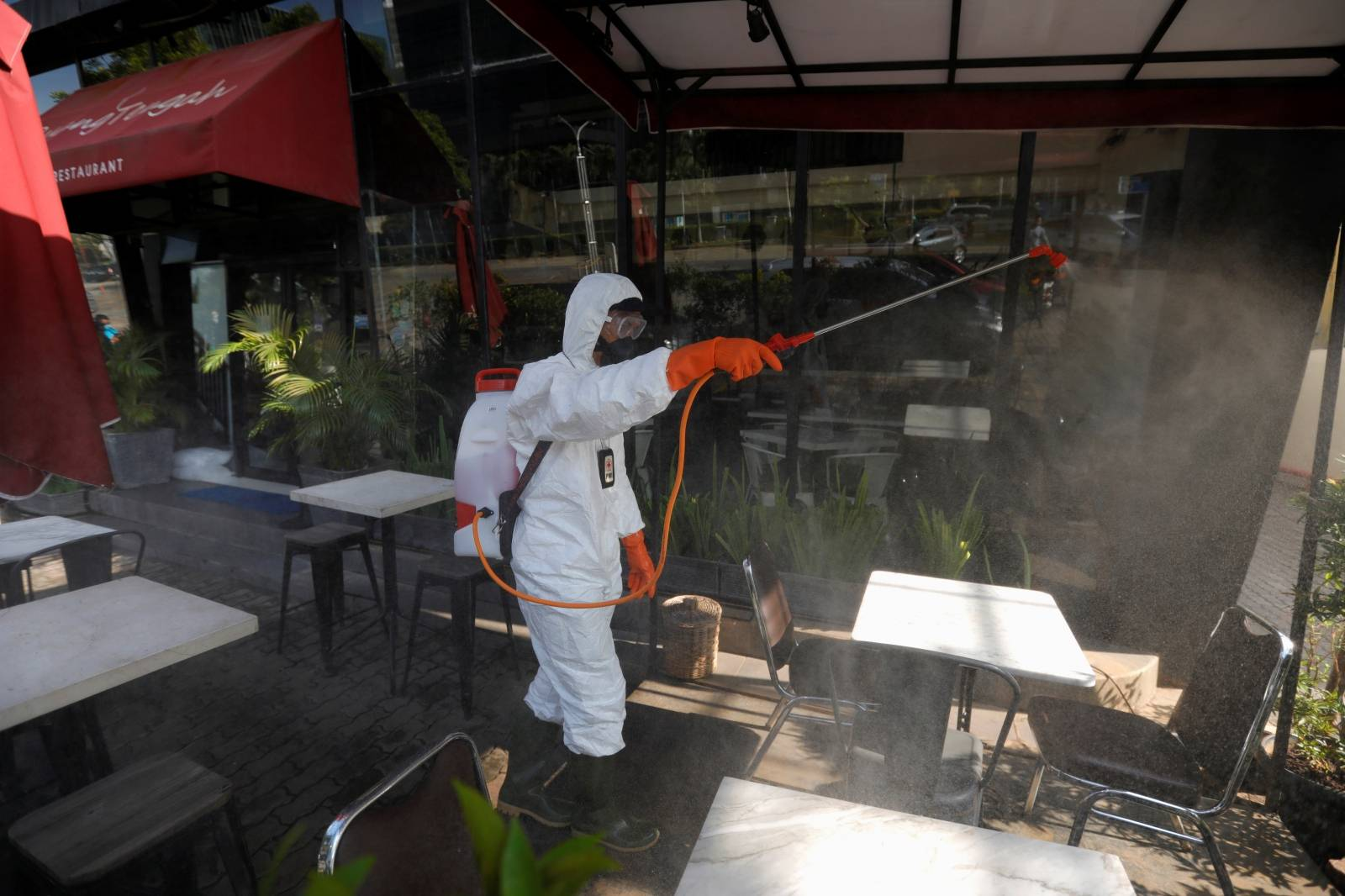 Indonesia's Red Cross personnel sprays disinfectant outside a restaurant at a department store amid the spread of coronavirus (COVID-19) in Jakarta