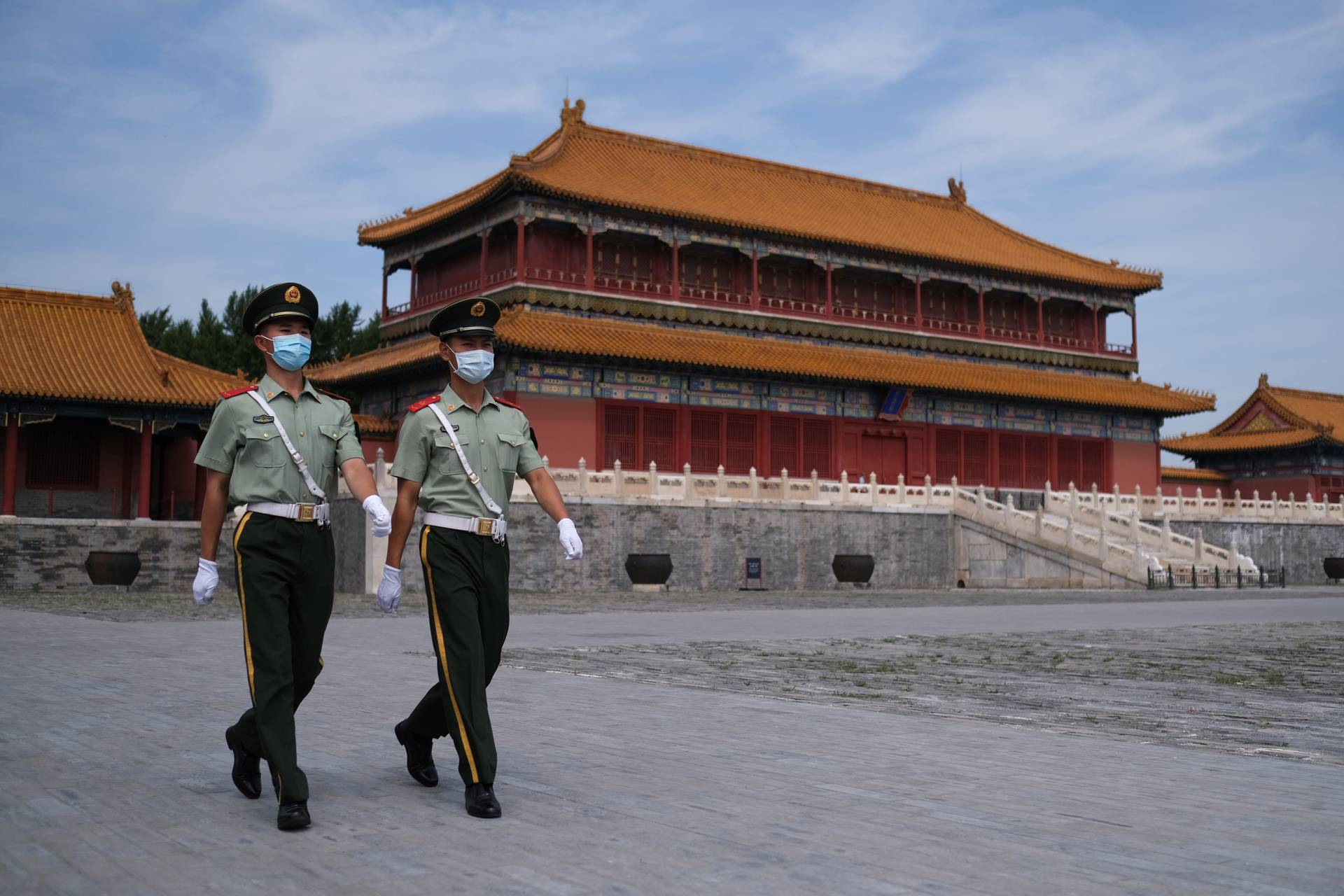 Paramilitary police officers wearing face masks walk at the Forbidden City following the outbreak of the coronavirus disease (COVID-19), in Beijing