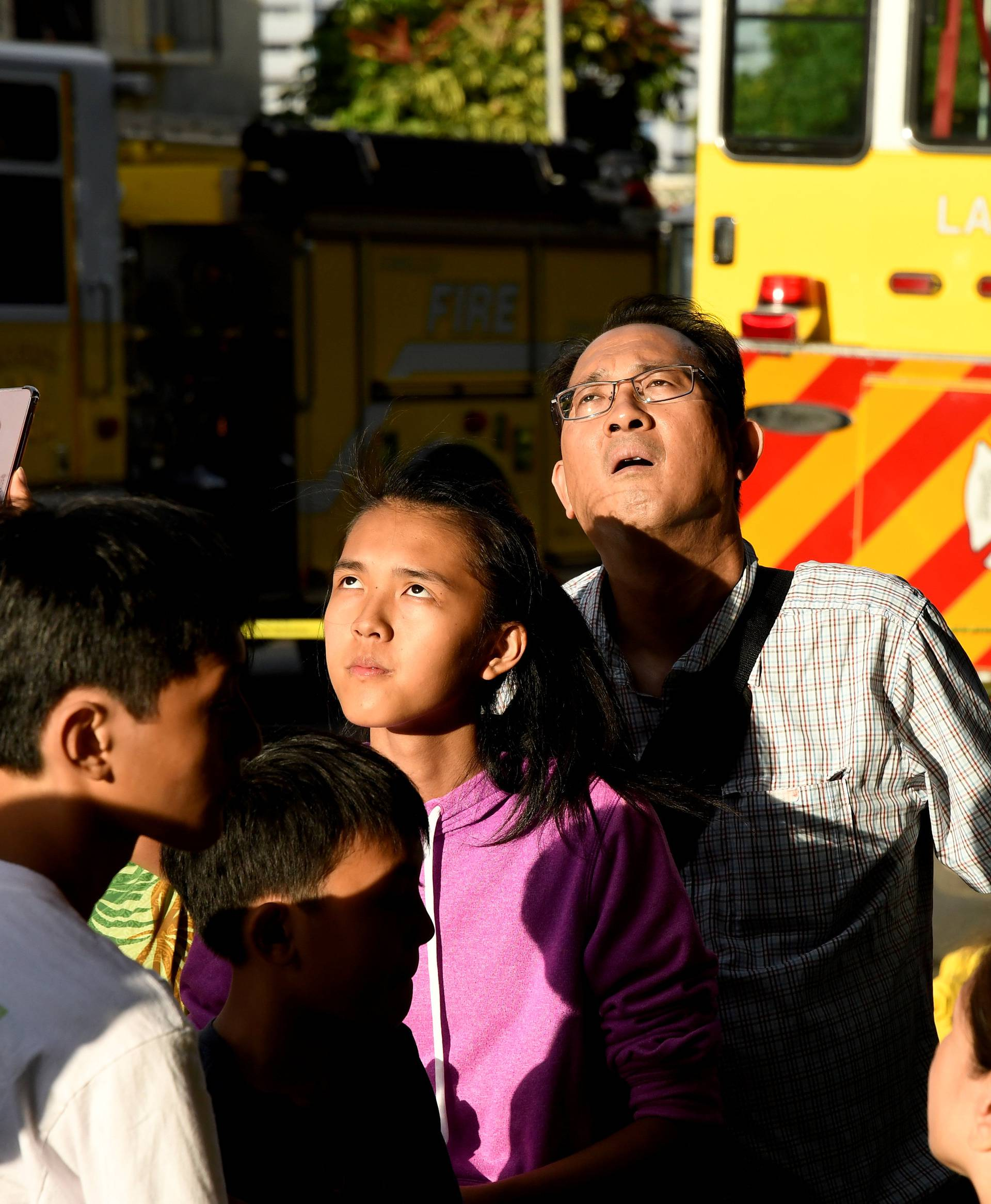 Evacuated residents look up at Marco Polo apartment building after a fire broke out in it in Honolulu, Hawaii.