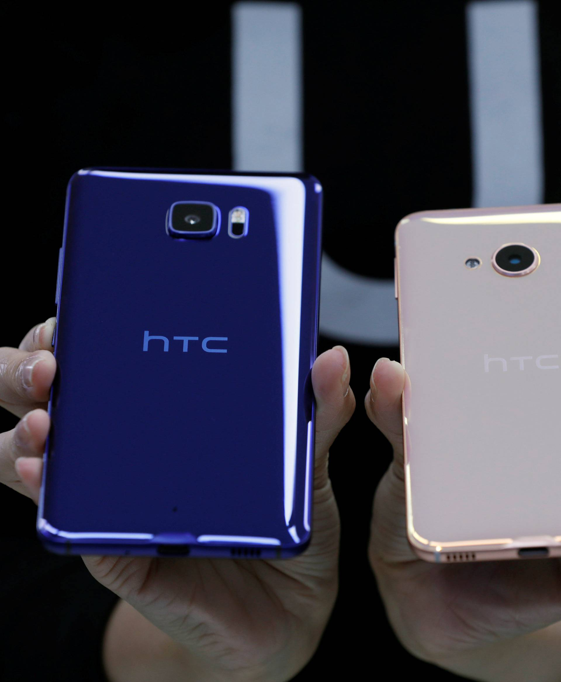 """A member of staff poses with a new HTC smartphone """"U Ultra"""" and """"U Play"""" after their launch event in Taipei"""