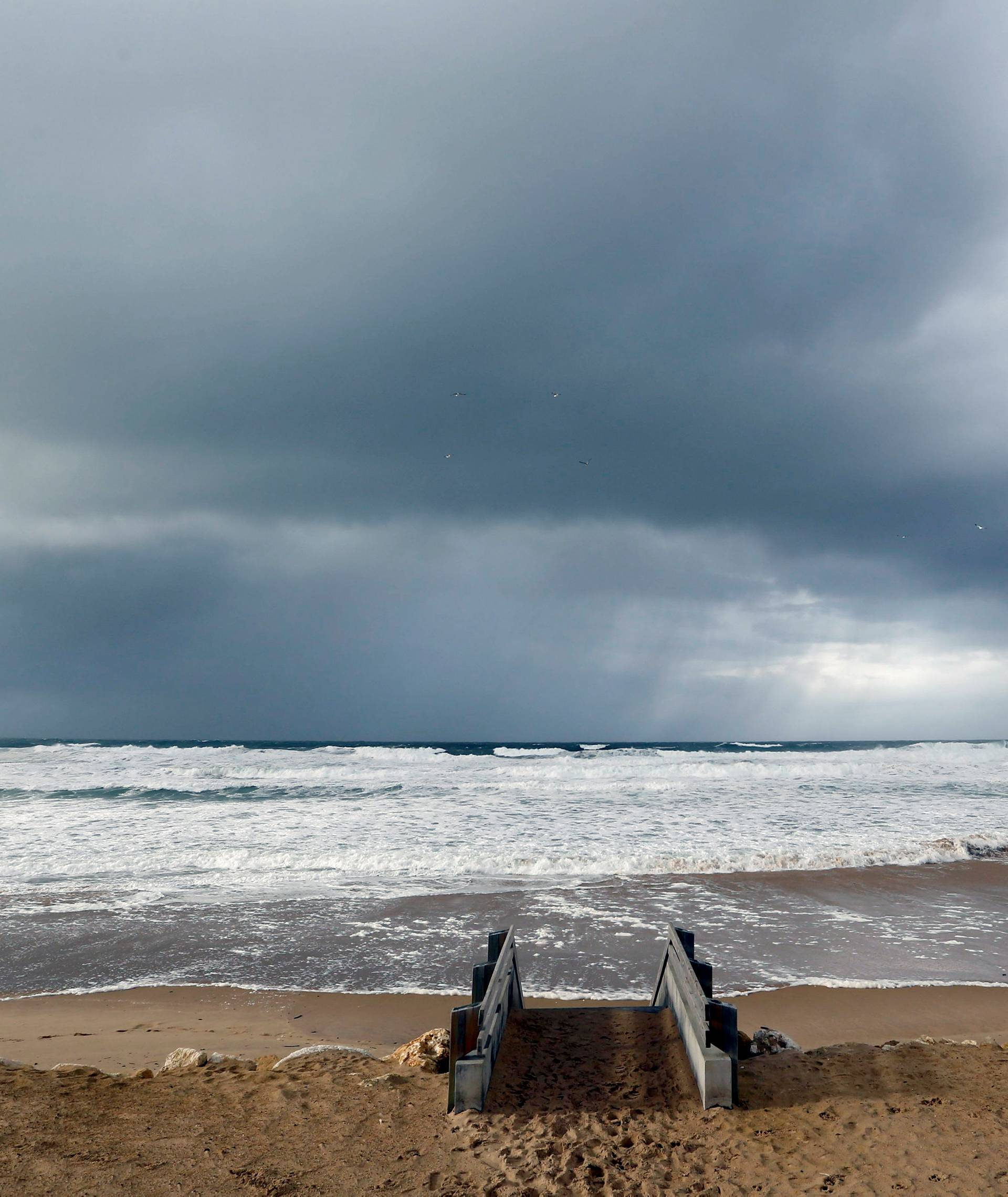 Clouds hang in the sky above the Atlantic ocean as waves from an early winter storm covers the beachfront in Lacanau