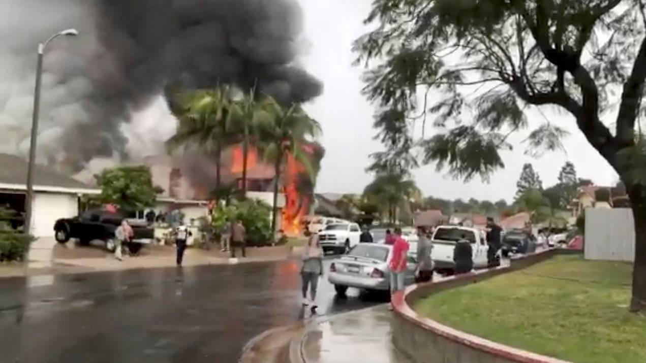 People look as smoke billows after a plane crashed into a house in a residential neighborhood in Yorba Linda, California