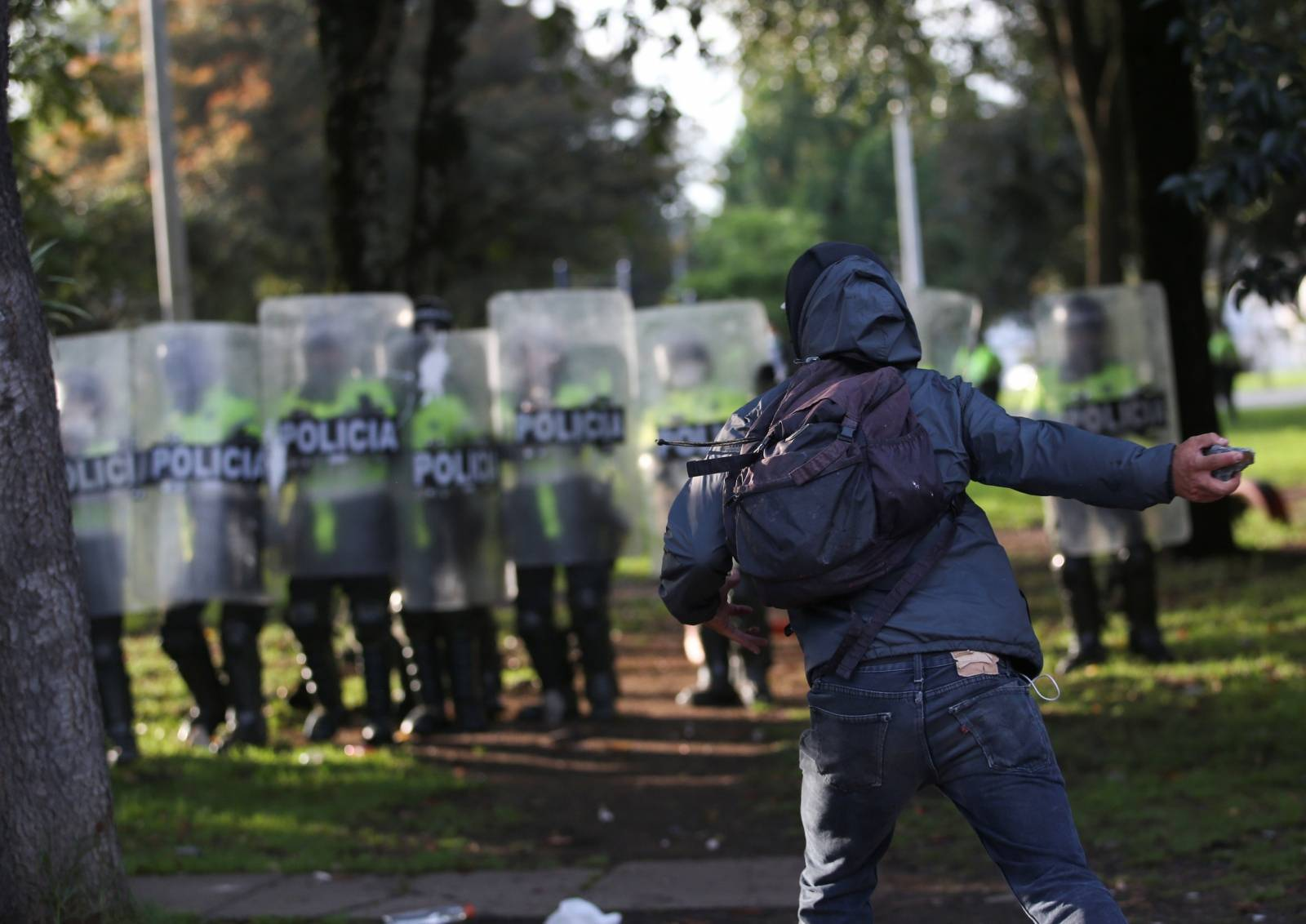 A demonstrator faces police during clashes after a man, who was detained for violating social distancing rules, died from being repeatedly shocked with a stun gun by officers, according to authorities, in Bogota