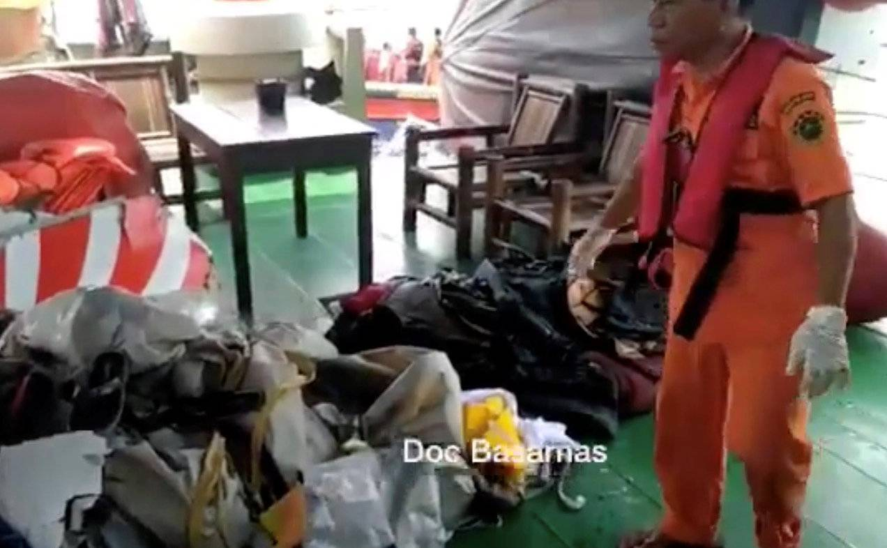 A Basarnas crew member gathers debris which are believed to be from Lion Air flight JT610, that took off from Jakarta and crashed into the sea
