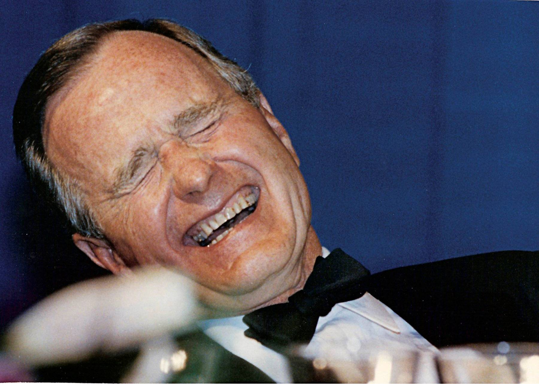 FILE PHOTO: U.S. President George H.W. Bush laughs while attending the annual White House Correspondents Association Awards dinner in Washington