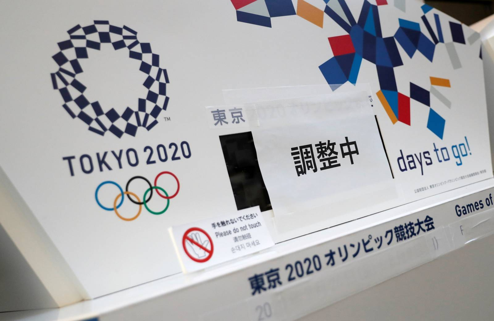 FILE PHOTO: Countdown clocks for the opening of Tokyo 2020 Olympic and Paralympic Games that are currently covered with banners that read 'Adjusting' are seen after postponing Games due to the outbreak of coronavirus disease (COVID 19), in Tokyo