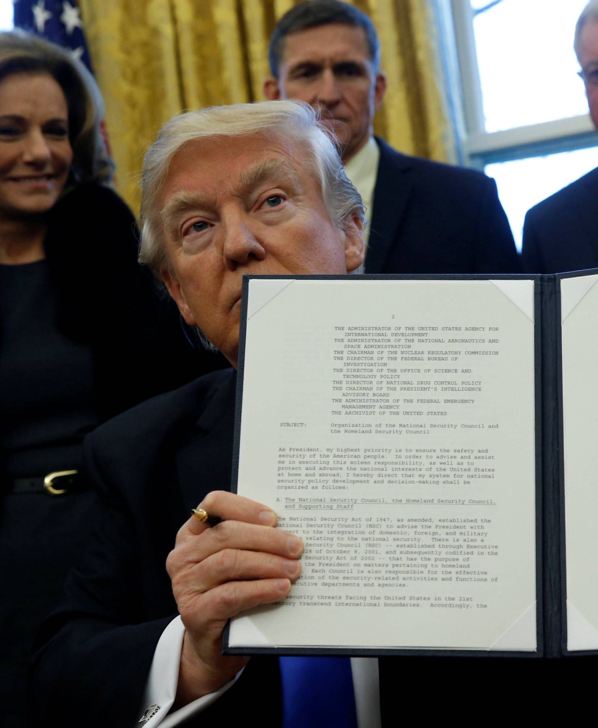Trump holds an executive order dealing with the structure of the National Security Council after signing it in the Oval Office at the White House in Washington