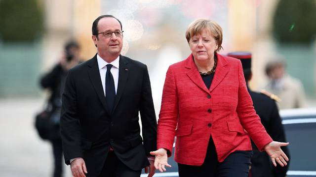 French President Francois Hollande welcomes German Chancellor Angela Merkel during arrivals for a Franco-German-Italian-Spanish summit ahead of the upcoming EU Summit in Versailles