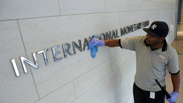 Staff cleans signage at International Monetary Fund headquarters in Washington