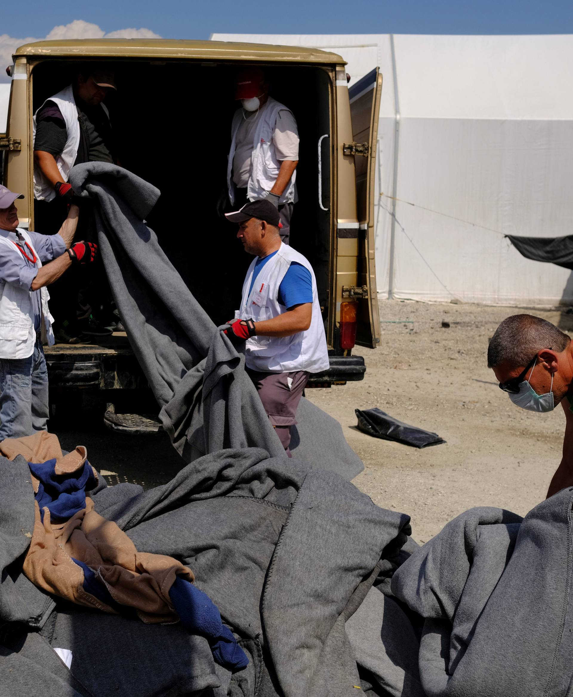 Workers remove blankets used by migrants during a police operation to evacuate a migrants' makeshift camp at the Greek-Macedonian border near the village of Idomeni