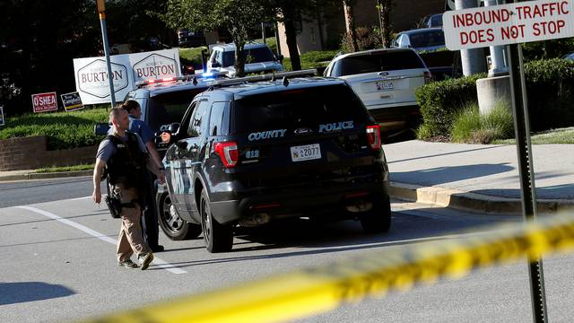 Police walk past a vehicle near a shooting scene at the Capital Gazette newspaper in Annapolis